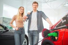 Ung le köpande första elbil för familj i visningslokalen Attraktiv tangent för maninnehavbil, medan stå mellan royaltyfri fotografi