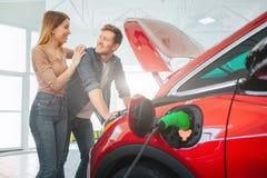 Ung le köpande första elbil för familj i visningslokalen Attraktiva par är tycker om för att köpa envänskapsmatch bil royaltyfri fotografi