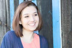 Ung le kvinna för stående på wood bakgrund Fotografering för Bildbyråer