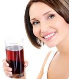 Ung le kvinna med exponeringsglas av körsbärsröd fruktsaft Arkivfoton