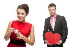Ung le kvinna och stilig man som rymmer röd hjärta på vit Arkivfoto