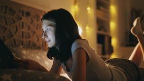 Ung le kvinna som använder minnestavladatoren för att dela socialt massmedia som hemma ligger i säng på natten Arkivbild