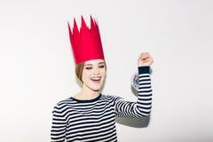 Ung le kvinna som firar partiet, den bärande avrivna klänningen och den röda pappers- kronan, lycklig dynamisk karnevaldiskoboll Royaltyfri Foto