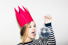 Ung le kvinna som firar partiet, den bärande avrivna klänningen och den röda pappers- kronan, lycklig dynamisk karnevaldiskoboll Arkivbilder