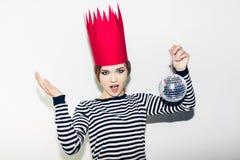 Ung le kvinna som firar partiet, den bärande avrivna klänningen och den röda pappers- kronan, lycklig dynamisk karnevaldiskoboll Royaltyfria Foton