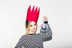 Ung le kvinna som firar partiet, den bärande avrivna klänningen och den röda pappers- kronan, lycklig dynamisk karnevaldiskoboll Royaltyfria Bilder