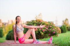 Ung le kvinna som utomhus gör sportiga övningar Kvinnlig konditionmodellutbildning utanför i parkera Sund wellness Royaltyfria Bilder