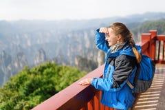 Ung le kvinnlig turist som tycker om fantastisk bergsikt royaltyfria bilder