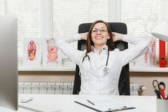 Ung le lycklig kvinnlig doktor som sitter på skrivbordet i ljust kontor i sjukhus Kvinnan i den medicinska kappan, stetoskop kopp royaltyfri foto