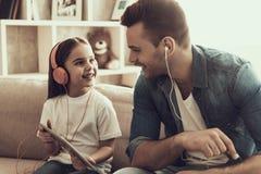 Ung le lyssnande musik för man och för liten flicka royaltyfri fotografi