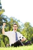 Ung le man som rymmer en boll och gör en gest lycka i Royaltyfri Foto