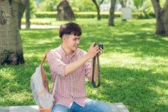Ung le man som tar bilden, medan gå in parkera Fotografering för Bildbyråer
