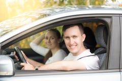 Ung le mankörning och kvinnasammanträde i bilen arkivbilder