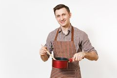 Ung le mankock eller uppassare i det randiga bruna förklädet, skjorta som rymmer den röda tomma stewpan träskeden som isoleras på arkivfoto