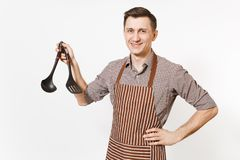 Ung le mankock eller uppassare i det randiga bruna förklädet, skjorta som rymmer den svarta sleven eller kökskeden, spatel som is arkivbild