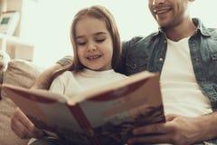 Ung le manläsebok till lilla flickan arkivbild