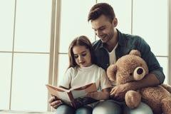 Ung le manläsebok till lilla flickan royaltyfri fotografi