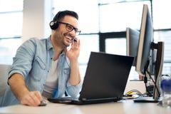 Ung le manlig appellmittoperatör som gör hans jobb med en hörlurar med mikrofon Stående av arbetaren för appellmitt på kontoret arkivfoto