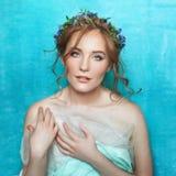 Ung le mjuk flicka med blåa blommor på ljus - blå bakgrund Stående för vårskönhet Royaltyfria Bilder