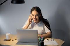 Ung le mobiltelefon och arbete för kvinna talande i afton Arkivfoton
