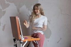 Ung le nätt blond flicka med borste- och palettanseende nära staffliteckningsbild Konst kreativitet arkivbild