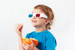 Ung le pojke i stereo- exponeringsglas som äter popcorn Royaltyfri Bild