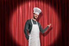 Ung le stilig kock i den vita hatten och förklädet som tänds upp av blickpunkt som gör att framlägga gest på den röda etappgardin fotografering för bildbyråer