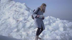 Ung ledsen blond nätt kvinna i det varma omslaget som halkar, medan gå på glaciären med översikten i händer Fantastisk natur av lager videofilmer