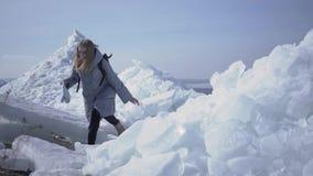 Ung ledsen blond nätt kvinna i det varma omslaget som halkar, medan gå på glaciären med översikten i händer Fantastisk natur av arkivfilmer