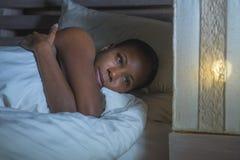 Ung ledsen deprimerad svart afrikansk amerikankvinna i för lidandefördjupning för säng sömnlösa känsliga desperata bekymrade sömn arkivfoton
