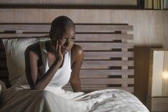 Ung ledsen deprimerad svart afrikansk amerikankvinna i för lidandefördjupning för säng sömnlösa känsliga desperata bekymrade sömn royaltyfria foton