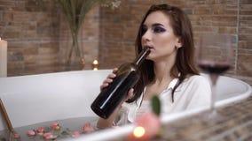 Ung ledsen kvinna med ljust makeupdrinkvin från flaskan som ligger i bad med blommor lager videofilmer