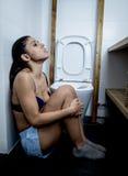 Ung ledsen och deprimerad bulimic kvinna som känner sjukt sammanträde på golvet av toalettbenägenheten på WC Arkivbild