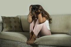 Ung ledsen och deprimerad kvinna i pyjamas p? den hemmastadda soffan som gr?ter desperat frustrerad och uppriven lidandesp?nning  royaltyfri bild