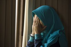 Ung ledsen och deprimerad muslimsk kvinna i för Hijab för islam opasslig lida fördjupning för traditionell huvud för halsduk hemm royaltyfri foto