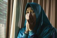 Ung ledsen och deprimerad muslimsk kvinna i för Hijab för islam opasslig lida fördjupning för traditionell huvud för halsduk hemm royaltyfri fotografi