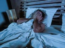 Ung ledsen och desperat man som ligger på säng som gråter den deprimerade beläggningframsidan med händer som lider fördjupningen  Royaltyfria Foton