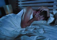 Ung ledsen och desperat man som ligger på säng som gråter den deprimerade beläggningframsidan med händer som lider fördjupningen  Arkivbild