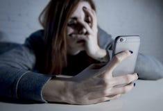 Ung ledsen sårbar flicka som använder den skrämde mobiltelefonen och desperat Arkivbild