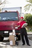 Ung leveransman som ser leveranslistan på skrivplattan med lastbilen i bakgrund Arkivbilder