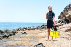Ung lgirl i dykningdräkt med skovlar som står på, vaggar kusten royaltyfri fotografi
