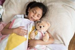 Ung liten asiatisk flicka som sover, medan krama nallebjörnen royaltyfria bilder