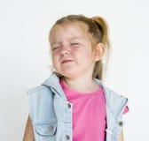 Ung liten flicka med den konstiga leendeuttrycksståenden royaltyfri bild