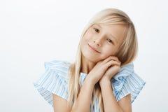 Ung liten flicka som gör den förtjusande framsidan för att få vad önskar Nöjt att bry sig ungt barn med blont hår som i huvudsak  Fotografering för Bildbyråer