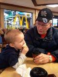 Ung litet barnpojke och hans morfar som äter på Mcdonalds Arkivfoton