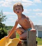Ung litet barnpojke som är osäker av att gå ner en simbassängglidbana Arkivfoto