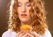 Ung lockig kvinna med en kaka royaltyfria bilder