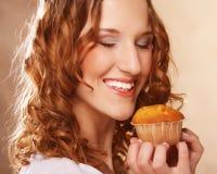 Ung lockig kvinna med en kaka royaltyfria foton