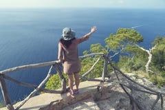 Ung lockig kvinna med hatten som vinkar på ett fartyg i havet arkivfoton