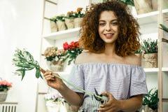 Ung lockig student som tycker om hennes deltids- jobb i flowershop royaltyfria foton